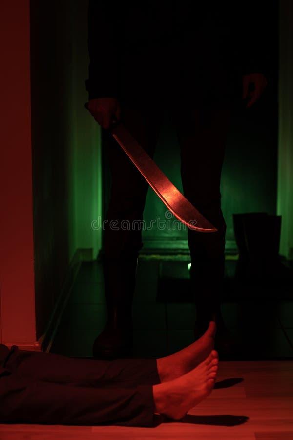 Bild av tjuven med machetet och mannen som ligger på golv i mörk lägenhet royaltyfri foto