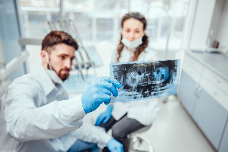 Bild av två doktorer som ser röntgenstrålen Fokus p? r?ntgenstr?le arkivfoton