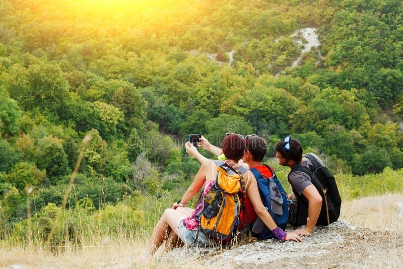 Bild av två män och kvinnan som tar selfie, medan sitta på backen med vegetation royaltyfri fotografi