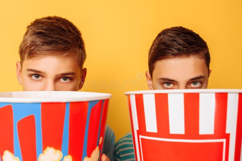 Bild av två skrämda tonåringar, grabbar som håller ögonen på en fasafilm och döljer bak en hink av popcorn på en gul bakgrund royaltyfri foto