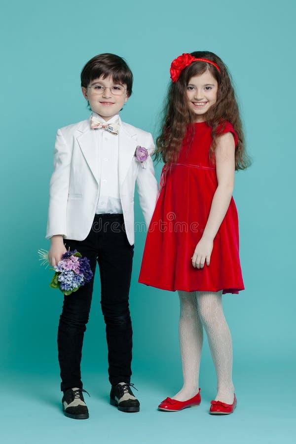 Bild av två ungar i elegant kläder som rymmer blommor, flicka i röd klänning som ler som isolerar på en blå bakgrund royaltyfria bilder