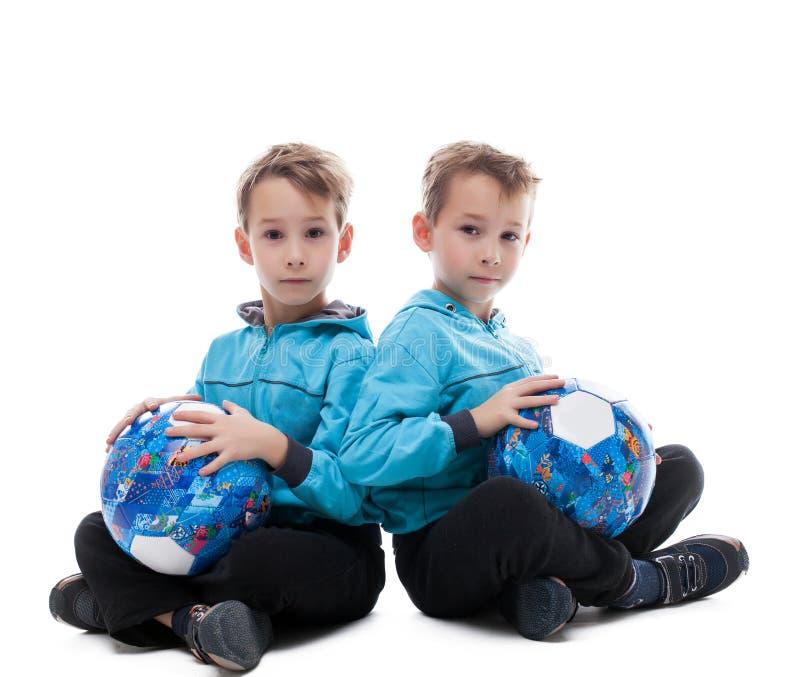 Bild av underhållande tvilling- bröder som poserar med bollar royaltyfri foto