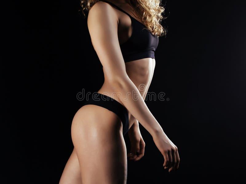 Bild av ung baksida för kvinnlig idrottsman nen på mörk bakgrund Konditionmodell som poserar i studio royaltyfria bilder