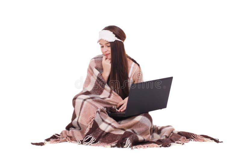 Bild av unga flickan med att sova maskeringen på hennes huvud Ordna till för att sova flickan med en bärbar dator arkivbild
