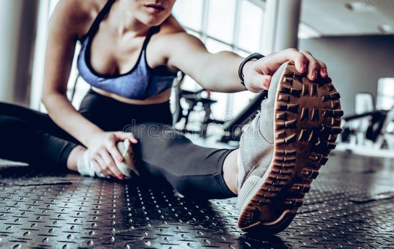 Bild av ursnyggt ungt konditionkvinnasammanträde i idrottshall nära fönster, medan gör sträckning av övningar royaltyfri foto
