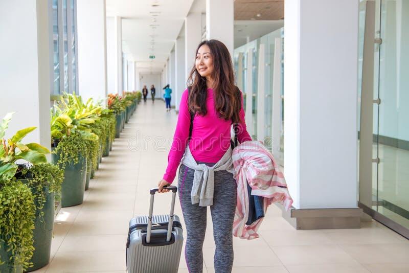 Bild der asiatischen Frauenreise allein tragen Koffer im Flughafen stockfoto