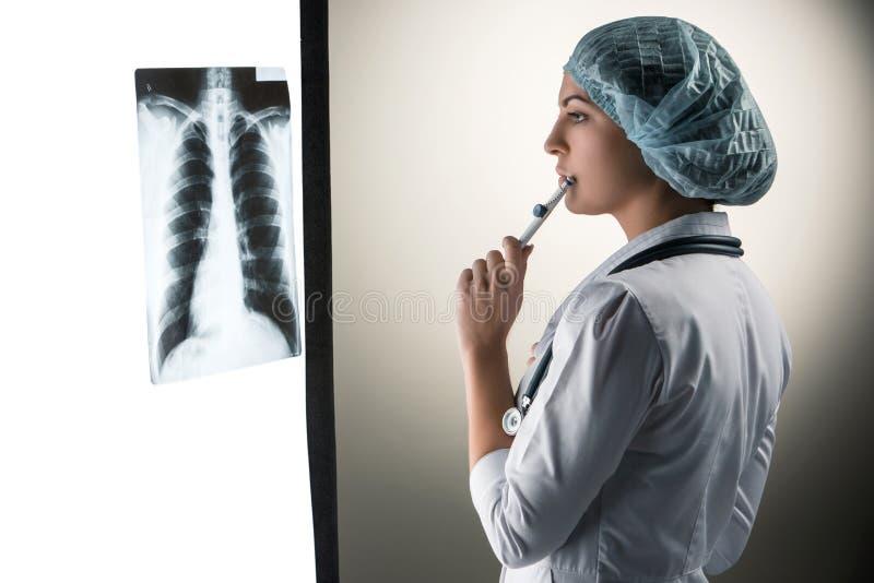 Bild der attraktiven Ärztin Röntgenstrahl betrachtend lizenzfreie stockfotos