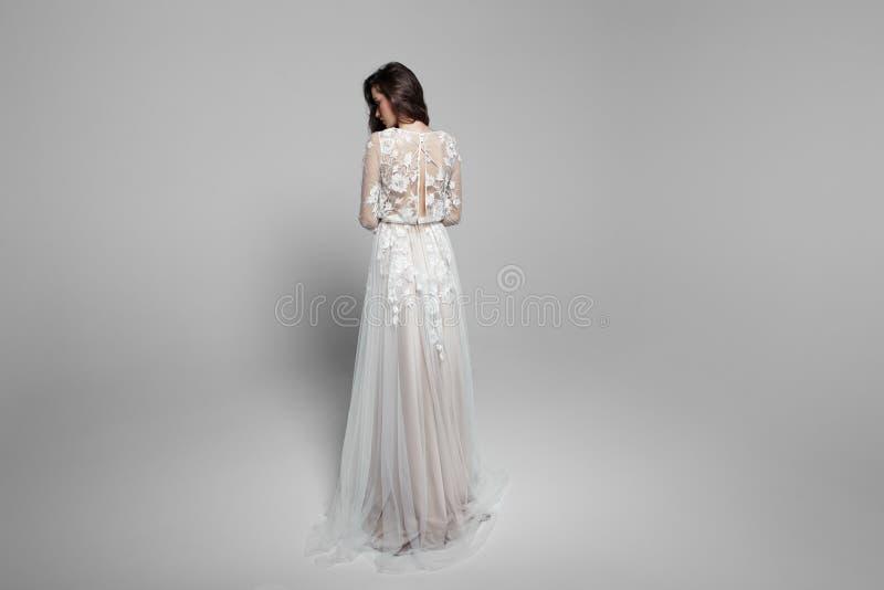 Bild der Braut von der Rückseite, würdevolle junge Frau im langen wendding Kleid, lokalisiert auf einem weißen Hintergrund lizenzfreie stockfotografie