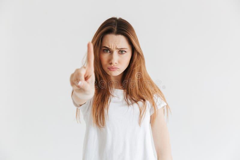 Bild der ernsten Frau im T-Shirt, das Zeigefinger an der Kamera zeigt stockfotografie