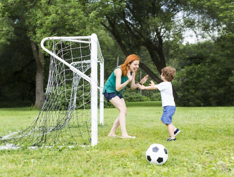 Bild der Familie, der Mutter und des Sohns, die Ball im Park spielen lizenzfreie stockfotos