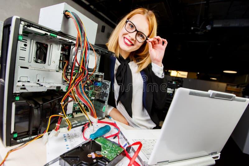 Bild der Frau in den Gläsern bei Tisch mit defektem Prozessor und Laptop stockfoto