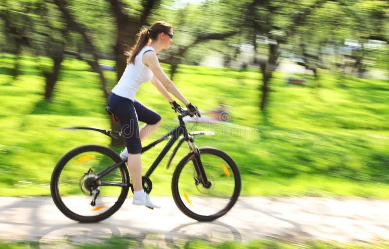 Bild der Frau mit Fahrrad in einem grünen Park lizenzfreie stockfotos