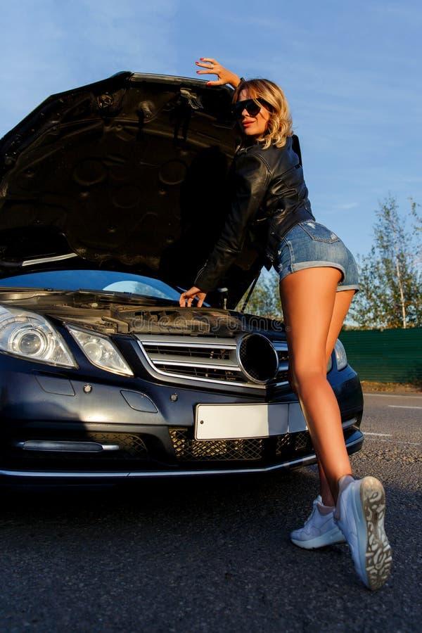 Bild der Frau nahe defektem Auto mit offener Haube auf Straße stockfoto