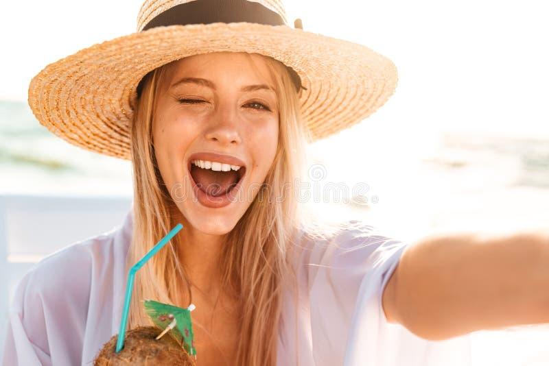 Bild der frohen hübschen Frau 20s im lachenden Sommerstrohhut, a lizenzfreies stockbild