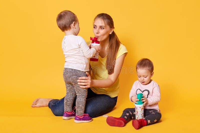 Bild der glücklichen Familie, Mama mit ihren netten Zwillingen, Mutterspiele mit ihren Kindern, Schwestern mögen Zeit mit ihrer stockfotos
