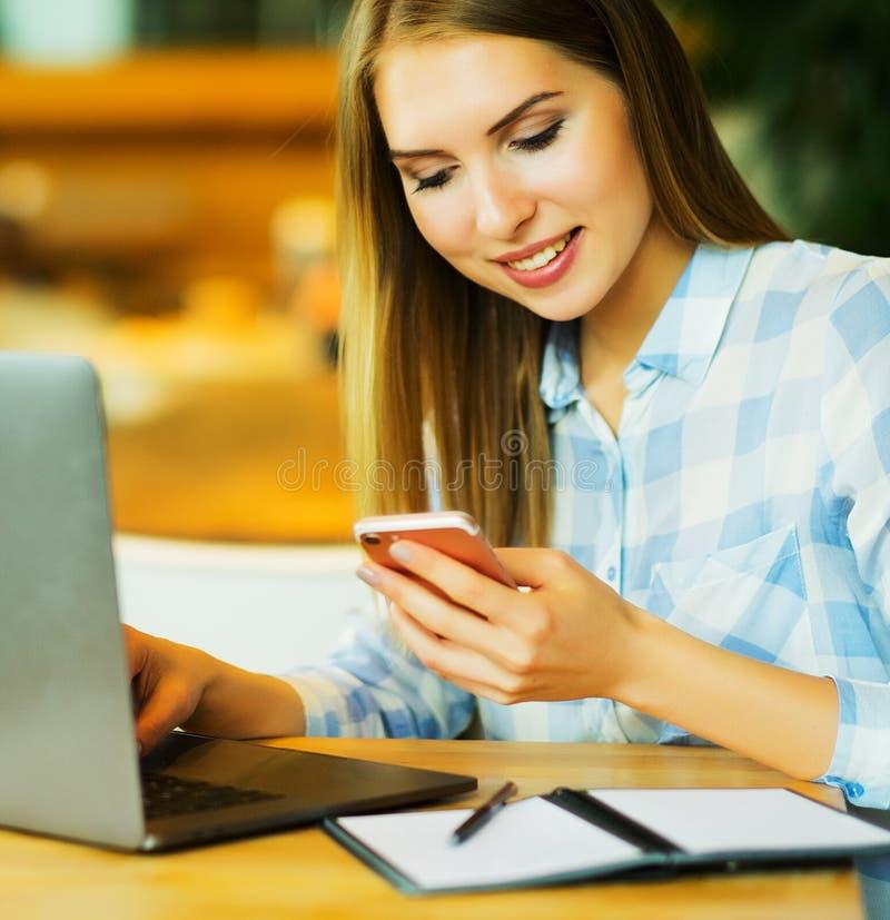 Bild der glücklichen Frau, die Laptop und Smartphone im Café verwendet Lifest stockbilder