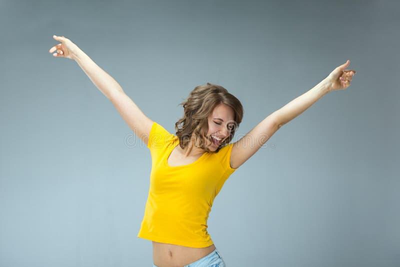 Bild der glücklichen jungen Frau, die gelbes Hemd und kurze Jeanshose trägt stockfotos
