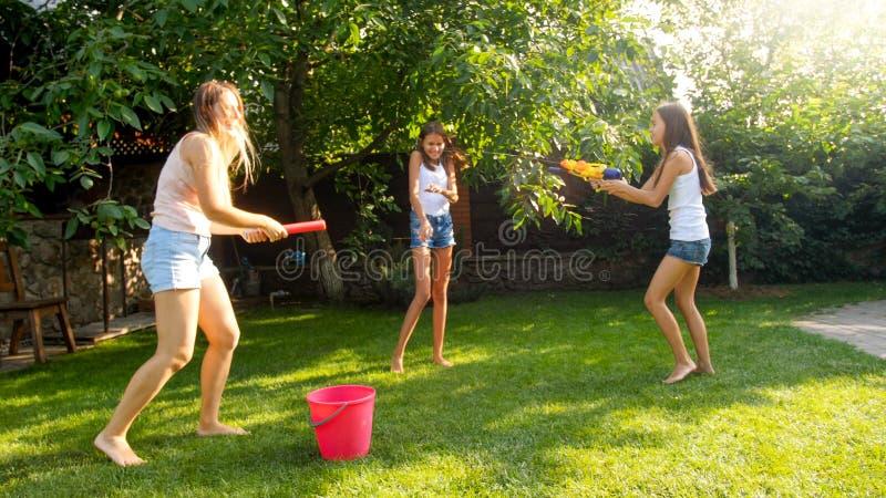 Bild der glücklichen netten Familie, die im Hinterhofgarten spielt Leutespritzwasser mit Wasserwerfern und Gartenschlauch lizenzfreie stockfotografie