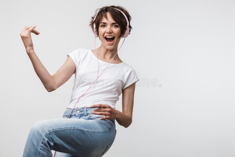 Bild der hübschen Frau im grundlegenden T-Shirt, das unsichtbare Gitarre beim Hören Musik mit Kopfhörern spielt lizenzfreie stockbilder