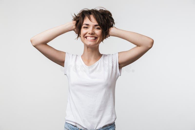 Bild der hübschen Frau mit dem kurzen Haar im grundlegenden T-Shirt ihren Kopf lachend und ergreifend stockfoto