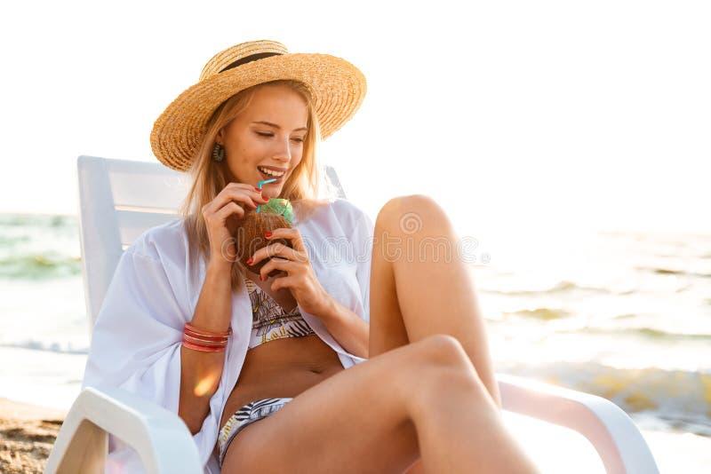 Bild der herrlichen kaukasischen Frau 20s in Strohhut trinkendem swee lizenzfreie stockfotos