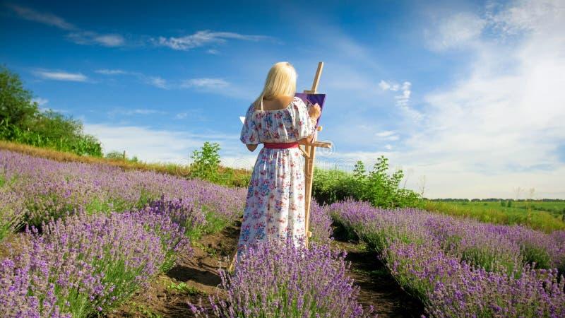 Bild der hinteren Ansicht des jungen weiblichen Künstlermalereibildes des Lavendelfeldes stockfotografie