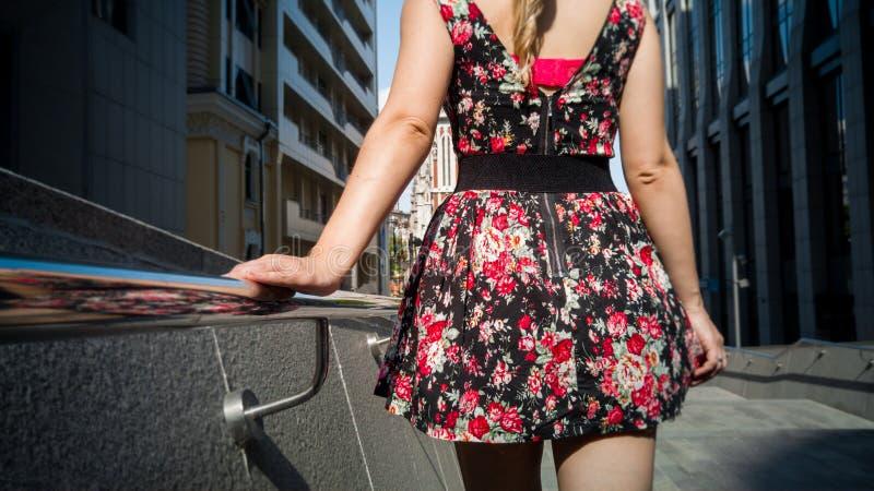 Bild der hinteren Ansicht der sexy Frau in der kurzen Kleiderholdinghand auf Metallhandlauf beim Gehen auf Straße lizenzfreie stockfotografie