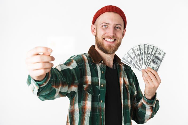Bild der Holdingkreditkarte des gut aussehenden Mannes und des Fans des Dollargeldes, bei der Stellung lokalisiert über weißem Hi lizenzfreie stockbilder