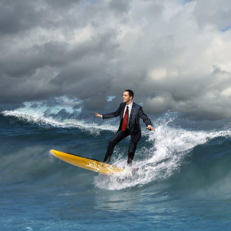 Junge Geschäftsperson, die auf die Wellen surft stockfotografie
