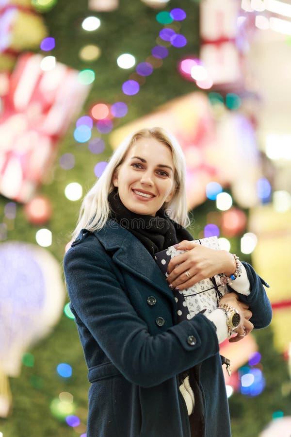 Bild der lächelnden Frau im Mantel mit Geschenkbox auf Hintergrund des Weihnachtsbaums im Speicher lizenzfreies stockbild