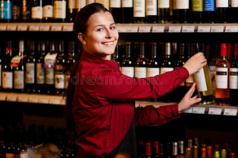 Bild der lächelnden Frau mit Flasche in ihren Händen in der Weinhandlung stockbild