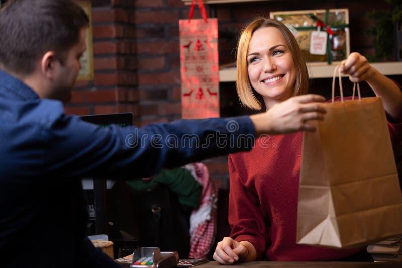 Bild der lächelnden Verkäuferfrau, die dem männlichen Käufer Papiertüte gibt lizenzfreie stockbilder