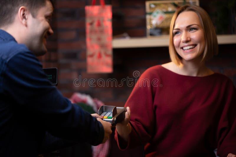 Bild der lächelnden Verkäuferfrauenstellung hinter Registrierkasse und männlichem Käufer von der Rückseite stockfotos