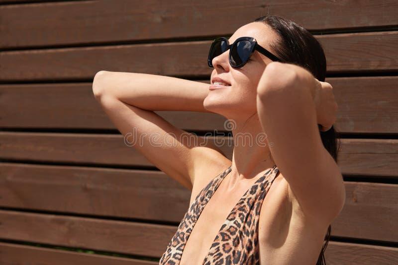 Bild der magnetischen attraktiven Modellaufstellung lokalisiert über hölzernem Hintergrund, tragender Leopardschwimmenanzug und m stockfoto