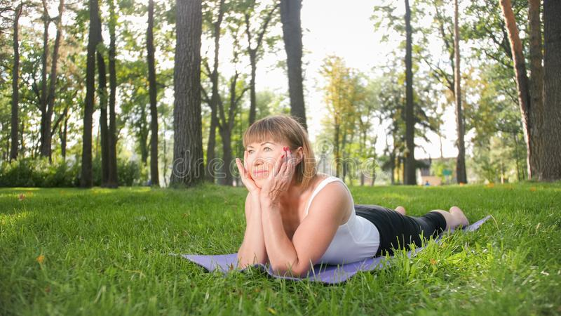 Bild der mittleren gealterten lächelnden glücklichen Frau, die Yogaübungen auf Gras an der Waldfrau sich kümmert um ihr meditiert lizenzfreie stockbilder
