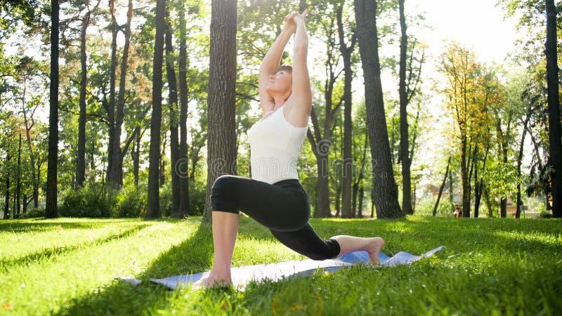 Bild der mittleren gealterten l?chelnden gl?cklichen Frau, die Yoga?bungen auf Gras an der Waldfrau sich k?mmert um ihr meditiert lizenzfreie stockbilder