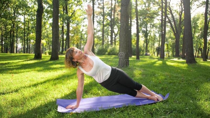 Bild der mittleren gealterten l?chelnden gl?cklichen Frau, die Yoga?bungen auf Gras an der Waldfrau sich k?mmert um ihr meditiert stockbild