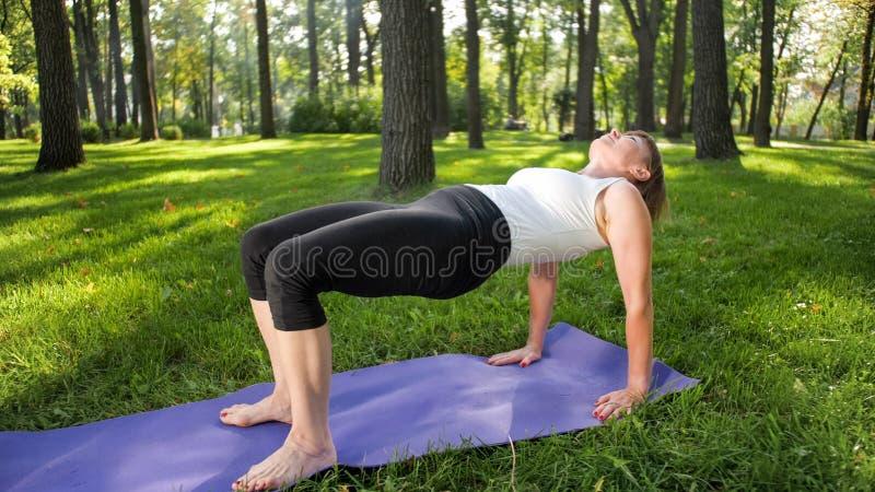 Bild der mittleren gealterten l?chelnden gl?cklichen Frau, die Yoga?bungen auf Gras an der Waldfrau sich k?mmert um ihr meditiert lizenzfreies stockbild