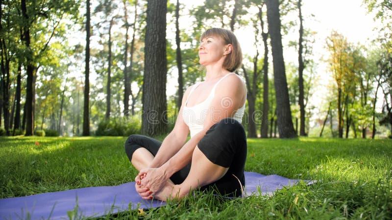 Bild der mittleren gealterten l?chelnden gl?cklichen Frau, die Yoga?bungen auf Gras an der Waldfrau sich k?mmert um ihr meditiert lizenzfreie stockfotos