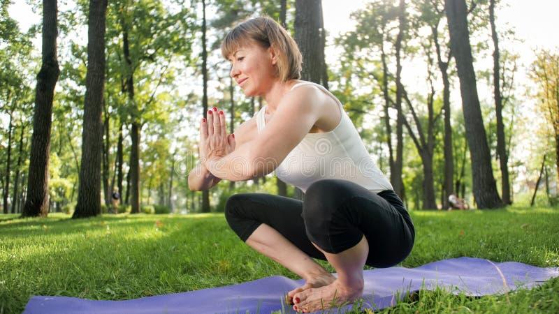 Bild der mittleren gealterten l?chelnden gl?cklichen Frau, die Yoga?bungen auf Gras an der Waldfrau sich k?mmert um ihr meditiert lizenzfreie stockfotografie