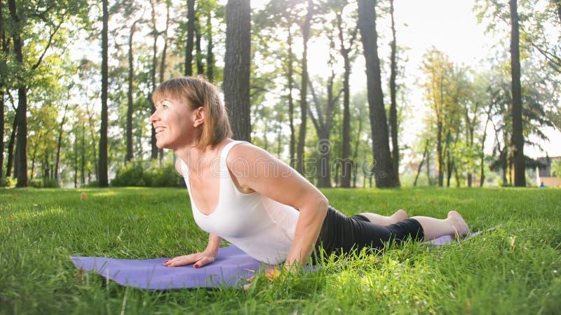 Bild der mittleren gealterten l?chelnden gl?cklichen Frau, die Yoga?bungen auf Gras an der Waldfrau sich k?mmert um ihr meditiert stockfotografie