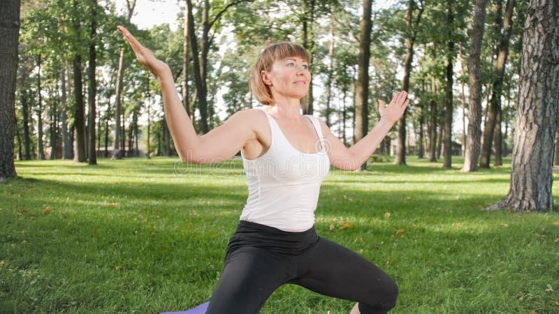 Bild der mittleren gealterten l?chelnden gl?cklichen Frau, die Yoga?bungen auf Gras an der Waldfrau sich k?mmert um ihr meditiert stockfoto