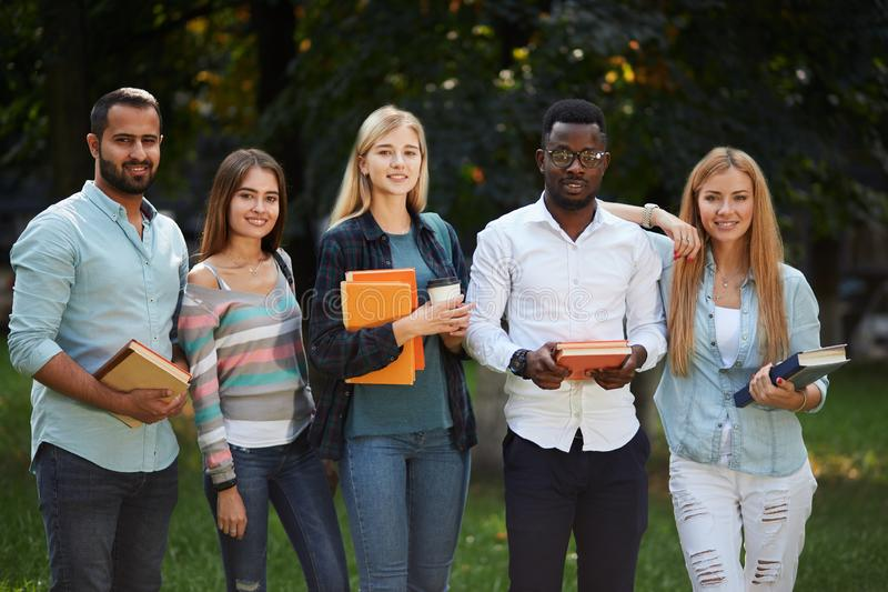 Bild der multiethnischen Gruppe Schulabgänger, die draußen stehen stockbilder