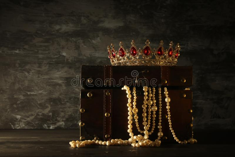 Bild der mysteriösen geöffneten alten hölzernen Schatztruhe mit Licht und Königin/König krönen mit roten Rubinsteinen Fantasie mi lizenzfreie stockbilder