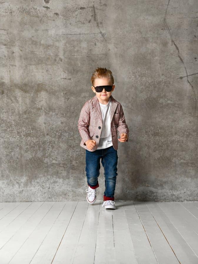 Bild der netten aufgeregten Stellung des kleinen Jungen Kinderlokalisiert über Betonmauer stockfotografie