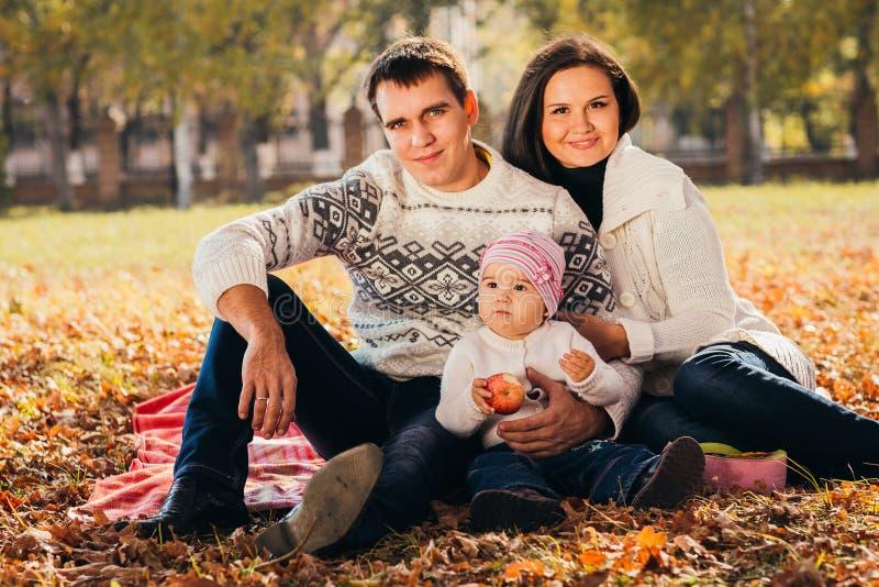 Bild der reizenden Familie im Herbstpark, junge Eltern mit den netten entzückenden Kindern, die draußen, frohe Natur fünf spielen lizenzfreie stockbilder