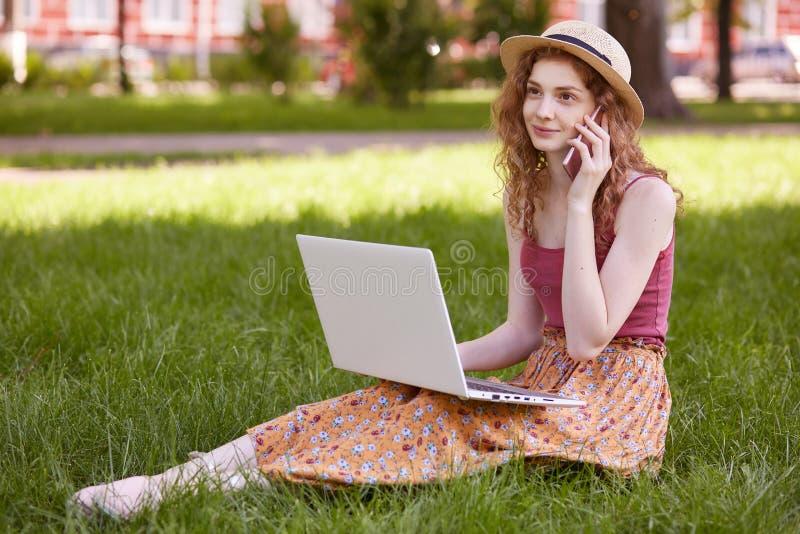Bild der schönen gelockten behaarten jungen Frau, die auf dem Gras, tragendem buntem Rock, roter Spitze und dem Strohhut, entspan stockbild