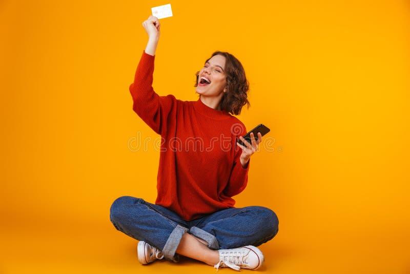 Bild der Schönheit, die Handy und Kreditkarte beim Sitzen auf dem Boden über gelbem Hintergrund verwendet lizenzfreie stockbilder