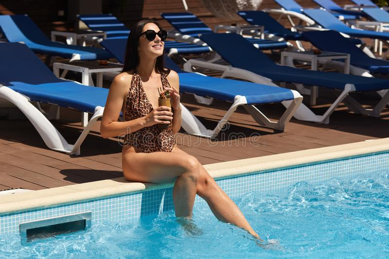 Bild der Schönheit entspannend im Swimmingpool Mädchen mit gesunder gebräunter Haut, herrliche weibliche genießende Sommerzeit am lizenzfreie stockbilder