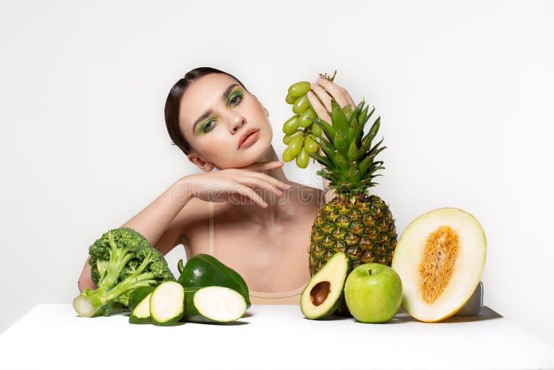 Bild der sch?nen jungen brunette Frau mit Obst und Gem?se auf dem Tisch, gr?ne Trauben in der Hand halten lokalisiert lizenzfreie stockfotos